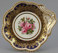 A single handled bone china dessert dish painted with roses in the centre by Frederick